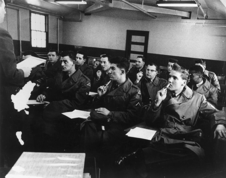 Singer Elvis Presley (1935 - 1977) in a classroom when in the Army.   (Photo by Keystone/Getty Images)