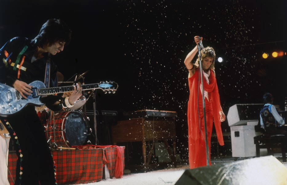 British rock stars Ron Wood (left) and Rod Stewart on stage during a concert by The Faces, circa 1974. On the extreme right is keyboard player Ian McLagan. (Photo by Keystone/Hulton Archive/Getty Images)