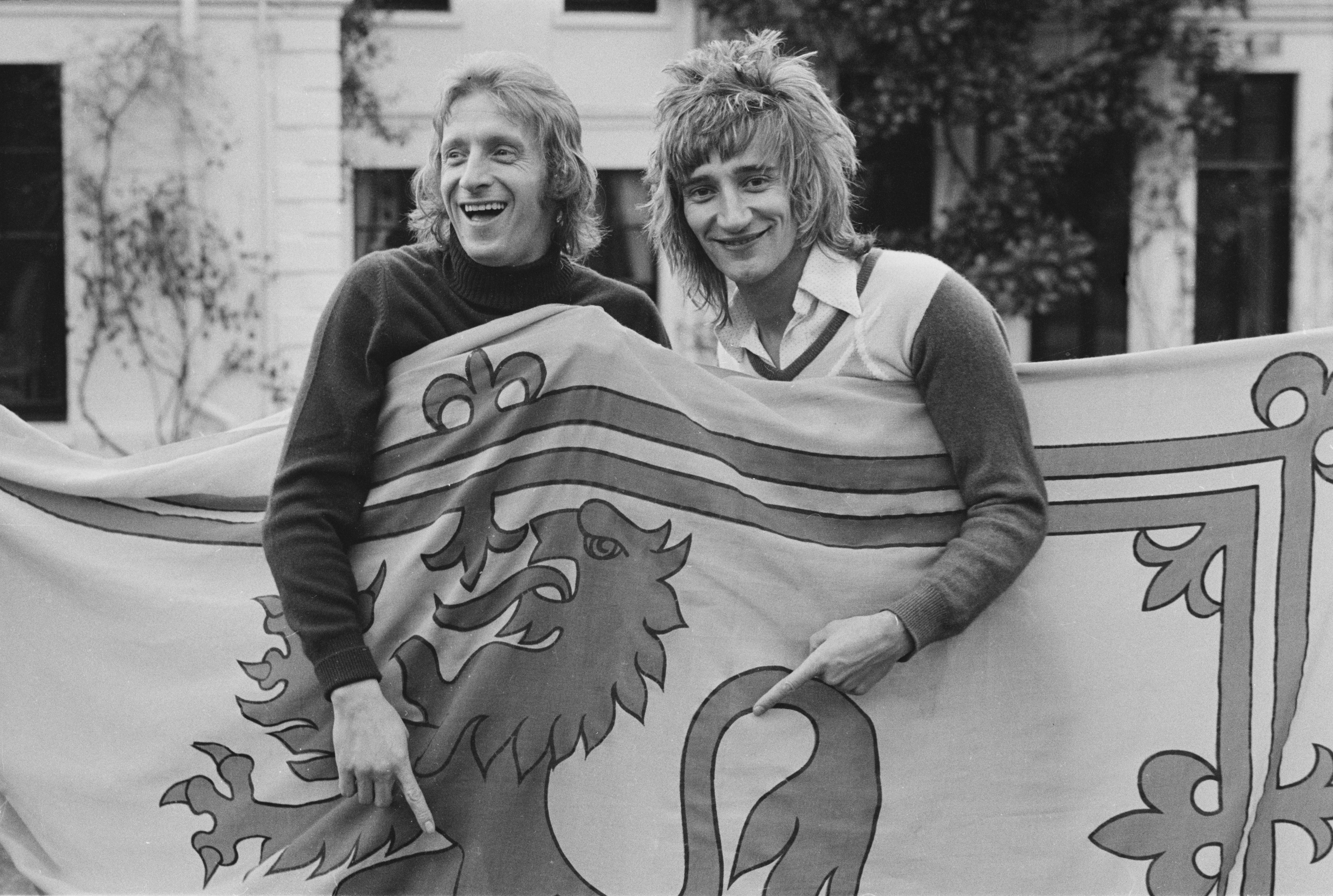 Scottish soccer player Denis Law of Manchester City FC with British singer-songwriter Rod Stewart, both are holding a Royal Banner of Scotland, UK, 18th March 1974. (Photo by B. Gomer/Daily Express/Hulton Archive/Getty Images)